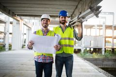 Construction engineer with foreman worker checking construction site stock photography