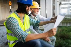 Construction engineer with foreman worker checking construction site. Construction engineer architect with foreman worker checking construction site royalty free stock photography