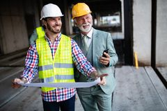 Construction engineer with foreman worker checking construction site. Construction engineer architect with foreman worker checking construction site royalty free stock photos