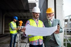 Construction engineer with foreman worker checking construction site stock photo