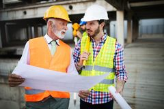 Construction engineer with foreman worker checking construction site. Construction engineer architect with foreman worker checking construction site royalty free stock image