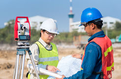 Construction engineer and foreman worker checking site. Construction engineer and foreman worker checking construction drawing at site for new Infrastructure stock image