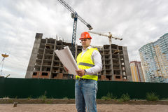 Construction engineer in hardhat on building site with working c royalty free stock photo