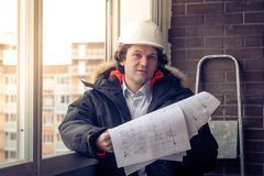 Construction engineer in hardhat with project in hands. Soft focus, toned. Stock Image