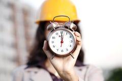 Construction engineer holding alarm clock royalty free stock photo