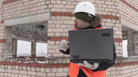 Construction engineer with laptop give directions to the worker stock video footage