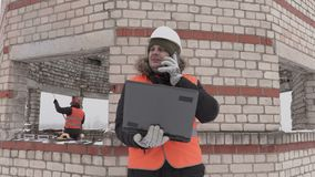 Construction engineer with laptop talking on smart phone near unfinished building. In winter day stock video
