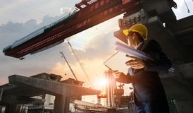 Construction engineer manager supervising progress of BTS Station Construction Project and tablet with blueprint in hands. Cranes royalty free stock images