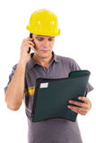 Construction engineer reading a document. Young construction worker speaking on cellphone while reading a document Royalty Free Stock Photography