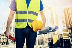 construction engineer with blueprint rolls at building site Royalty Free Stock Images