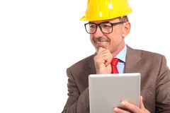 Construction engineer with tablet pad looks to side and smiles Royalty Free Stock Photos