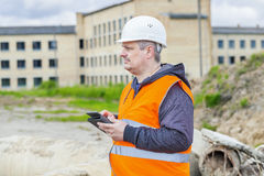 Construction Engineer with tablet PC near building. In summer day Stock Image