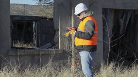 Construction engineer with tablet PC near destroyed building. Winter  day stock video