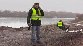 Construction engineer talking on cell phone and worker behind sorting paving bricks stock footage