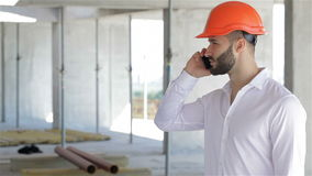 Construction engineer talking on the phone at the building under construction stock footage