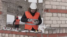 Construction engineer talking on smart phone and walking in unfinished building. In winter day stock footage