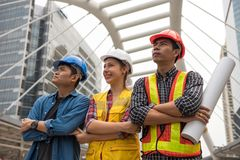 Construction Engineer team in city. Engineer team of Asian men and American women gather hands after constructed site complete or success. International Teamwork royalty free stock image