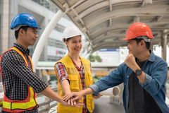 Construction Engineer team stacking hands. Engineer team of Asian men and American women stacking hands to encourage each other. International joint venture to royalty free stock images