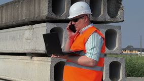 Construction Engineer using phone and laptop. In summer day stock video