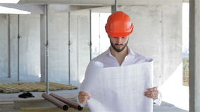 Construction engineer walks through the building under construction. Bearded construction engineer walking through the building under construction. Male builder stock video