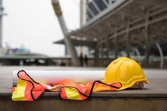 Construction engineer worker equipment in town. Safety yellow helmet hats, blueprint paper project, and worker dress on concrete floor at modern city with Stock Images
