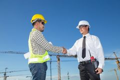Construction engineer with worker shaking hands at construction royalty free stock photos