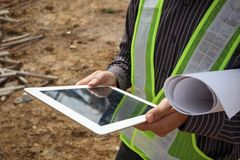 Construction engineer worker using tablet computer. Asian business man construction manager and engineer worker in protective helmet hold blueprints paper on Stock Photos