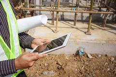 Construction engineer worker using tablet computer. Asian business man construction manager and engineer worker in protective helmet hold blueprints paper on Royalty Free Stock Photos