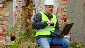 Construction Engineer working with PC and drinking tea stock video footage