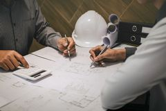 Construction engineering or architect discuss a blueprint while checking information on drawing and sketching, meeting for stock photography