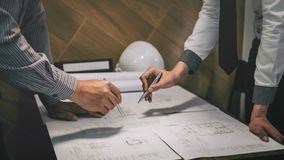 Construction engineering or architect discuss a blueprint while checking information on drawing and sketching, meeting for royalty free stock photography