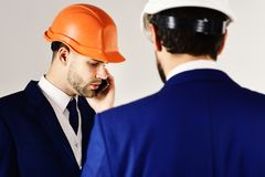 Construction, engineering, business, architecture, partnership, profession concept. Engineers in helmets with serious. Faces. Architects discuss project royalty free stock images
