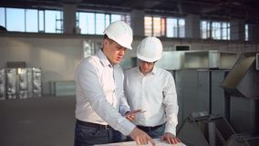 Construction Engineers Consult With Touchscreen Tablet For Building Development Planning Meeting insite. slow-motion. Construction Engineers Consult With stock video footage