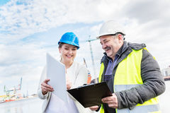 Construction engineers discussing documents in a port. Royalty Free Stock Image