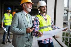 Construction engineers discussion with architects at construction or building site stock photo