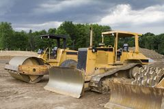 Construction Equipment. Construction Machinery - dozers, earthmovers, etc. on construction site - stormy sky royalty free stock photo