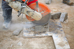Construction equipment. Cutting concrete slab worker uniforms boots working chainsaw acute angle royalty free stock photography