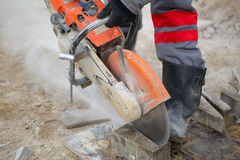 Construction equipment. Cutting concrete slab worker uniforms boots working chainsaw acute angle royalty free stock image