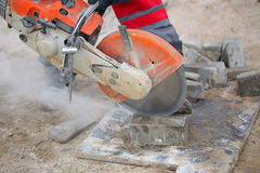 Construction equipment. Cutting concrete slab worker uniforms boots working chainsaw acute angle royalty free stock photo