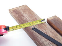 Measuring tape, wood and saw Royalty Free Stock Photos