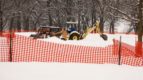 Construction Equipment Snowed In. Excavator and wheel loader is a couple of feet of snow behind orange plastic barrier. Shut down until springtime Stock Photos