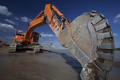 Construction excavator getting ready to scoop earth Stock Photo