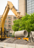Construction Excavator Lifting Concrete pipes. A construction excavator rigged for lifting concrete pipes moving some of them around at a sewer repair worksite royalty free stock photography