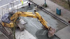 Construction excavator taking asphalt back and forth on the road stock video