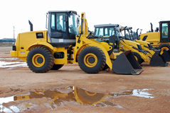 Construction excavators. Side view of modern yellow excavators parked in construction stock yard Stock Images
