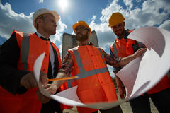 Construction Experts on Site. Low angle portrait of three workmen Royalty Free Stock Photography