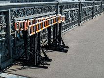 A construction fence for blocking traffic is on a bridge in the. Construction fencing for overlapping the passage of black metal with white and orange stripes stock photos