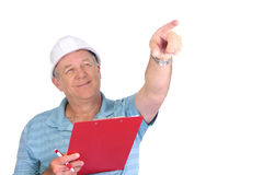 Construction Foreman. Middle aged construction foreman with hard hat pointing and smiling royalty free stock image