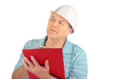 Construction Foreman. Serious middle aged construction foreman with hard hat writing on clipboard stock photos