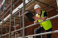 Construction Foreman Builder on Building Site With Clipboard. Male builder foreman, construction worker or site manager holding a clipboard, wearing a white royalty free stock photos
